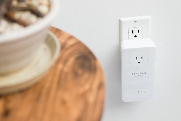 The TL-WPA8630P, a larger plastic plugin extender, which has a three-prong plug in the top center.