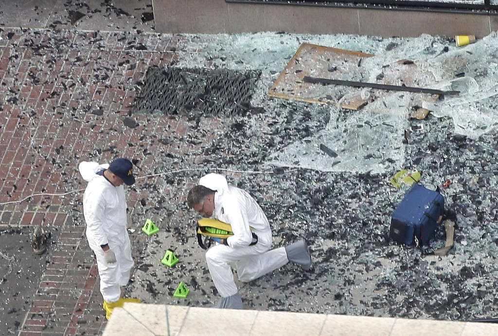 Two men in hazardous materials suits put numbers on the shattered glass and debris as they investigate the scene at the first bombing on Boylston Street in Boston Tuesday, April 16, 2013 near the finish line of the 2013 Boston Marathon, a day after two blasts killed three and injured over 170 people (photo credit: Elise Amendola/AP)
