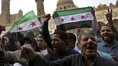 Protesters chant slogans and wave revolutionary flags during a rally after Friday prayers at al-Azhar Mosque in Cairo, Egypt, December 28, 2012. (AP/Khalil Hamra)