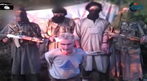In this still image from video published on the Internet on Wednesday, Sept. 24, 2014, by a group calling itself Jund al-Khilafah, or Soldiers of the Caliphate, members of the group stand behind French mountaineer Herve Gourdel just before beheading him. (photo credit: AP Photo)