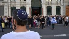 Un homme portant une kippa, regarde les gens prendre part à une manifestation appelée par le Conseil représentatif des institutions juives de France le 31 Juillet 2014 devant la synagogue de Lyon (Crédit : AFP / ROMAIN Lafabregue)