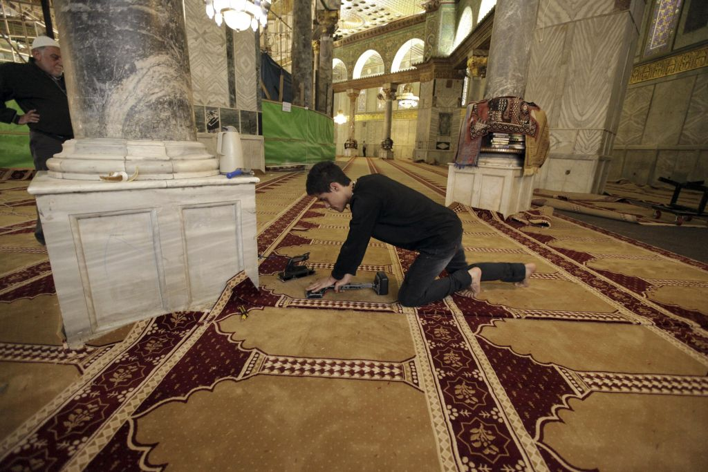 In this Sunday, April 19, 2015 photo, a worker places new carpets at the Dome of the Rock shrine in Jerusalem. (photo credit: AP Photo/Mahmoud Illean)