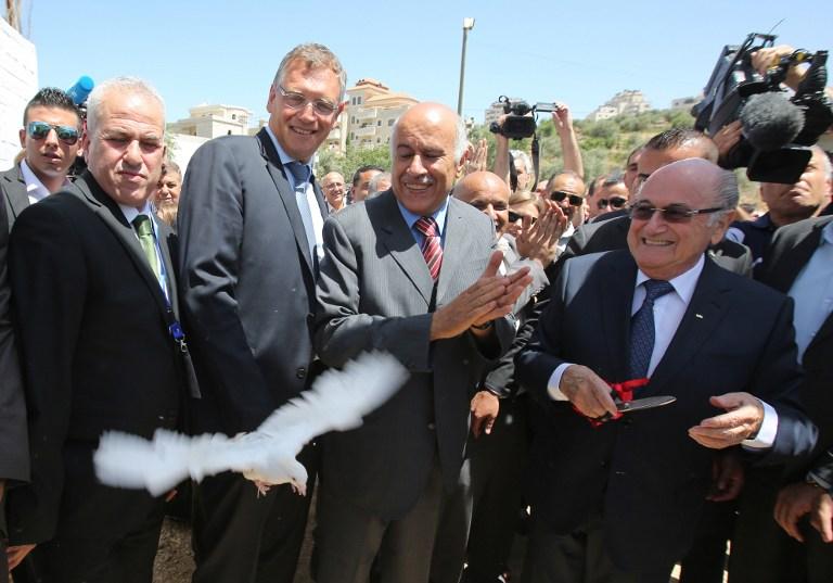 presidente de la FIFA, Joseph Blatter, derecha, lanza una paloma junto al presidente de la Asociación Palestina de Fútbol, Jibril Rajoub, durante su visita a Cisjordania el 20 de mayo de 2015. (AFP / ABBAS MOMANI)