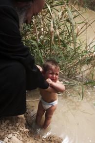 Un enfant est baptisé pendant la Pâque orthodoxe sur le site Qasr al-Yahud le 14 avril 2009 (Crédit : Matanya Tausig / flash 90)