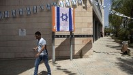 "An Israeli man walks past the Orange company logo covered with an Israeli flag at the ""Partner Orange"" Communications Company's offices in the city of Rosh Haayin, Israel. Thursday, June 4, 2015. (AP Photo/Dan Balilty)"