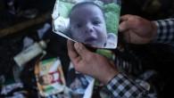 Un homme montre une photo de l'enfant palestinien Ali Saad Dawabsha de 18 mois qui est mort quand sa maison a été incendiée par des extrémistes juifs présumés dans le village cisjordanien de Duma le 31 juillet  2015 (Crédit photo:  Jaafar Ashtiyeh / AFP)