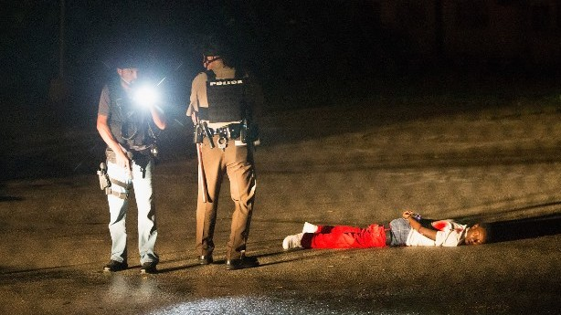 Police stand over Tyrone Harris after a shoot out along West Florissant Street during a demonstration to mark the one-year anniversary of the shooting of Michael Brown on August 9, 2015 in Ferguson, Missouri (Scott Olson/Getty Images/AFP)