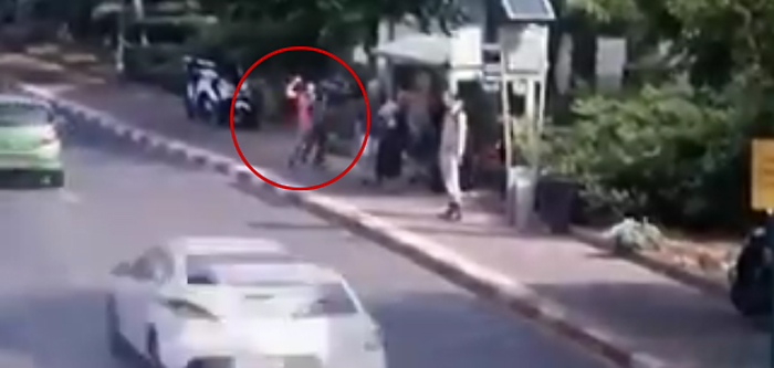 Still image from footage showing a knife-wielding terrorist (circled) stabbing Israelis as they wait at a bus stop on Jerusalem Boulevard in Ra'anana on October 12, 2015. (screen capture)