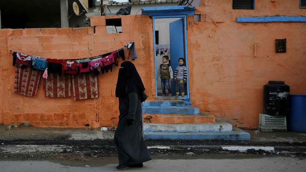 In this Tuesday, Dec. 15, 2015 photo, Palestinian children stand in a doorway of their home painted by artists in the Shati refugee camp in Gaza City. (AP Photo/Hatem Moussa)