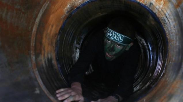 Un jeune Palestinien rampant dans un tunnel lors d'une cérémonie de remise des diplômes pour un camp d'entraînement dirigé par le Hamas le 29 janvier 2015, à Khan Yunis, dans le sud de la bande de Gaza (Crédit : AFP PHOTO / Saïd Khatib)