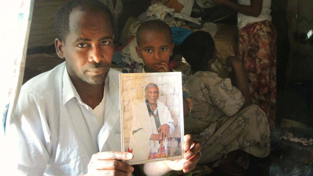 Simegnew Yosef Naga, 34, holds up a photo of his grandmother, who lives in Ramle, in his home in Gondar on April 15, 2016. (Melanie Lidman/Times of Israel)