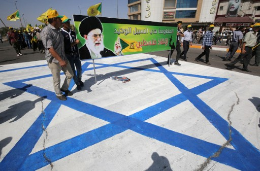 Iraqi men stand on an Israeli national flag and hold a banner depicting a portrait of Iran's supreme leader Ayatollah Ali Khamenei as they take part in a parade marking al-Quds (Jerusalem) Day in the capital Baghdad, on July 1, 2016. / AFP PHOTO / AHMAD AL-RUBAYE