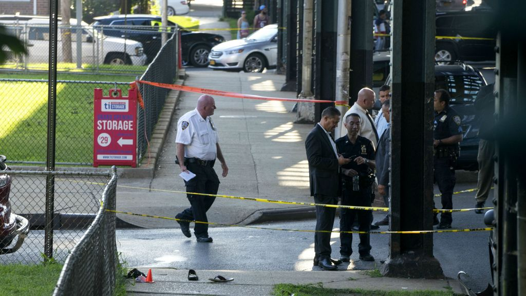 Sandals mark the crime scene, Saturday, Aug. 13, 2016, not far from the Al-Furqan Jame Masjid Mosque in the Ozone Park neighborhood of Queens, New York, where the leader of a New York City mosque and an associate were fatally shot in a brazen daylight attack. (AP Photo/Craig Ruttle)