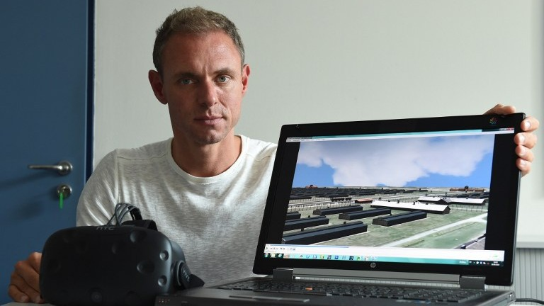 Ralf Breker of the Bavarian criminal police posing in Munich with virtual reality glasses and a computer which shows a picture from the 3D model of the former Nazi concentration camp Auschwitz, September 26, 2016. (AFP/Christof Stache)