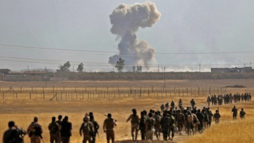 Smoke billows from an area near the Iraqi town of Nawaran, some 10km north east of Mosul, as Iraqi Kurdish Peshmerga fighters march down a dirt road on October 20, 2016, during the ongoing operation to retake the city from the Islamic State group. (AFP PHOTO / SAFIN HAMED)