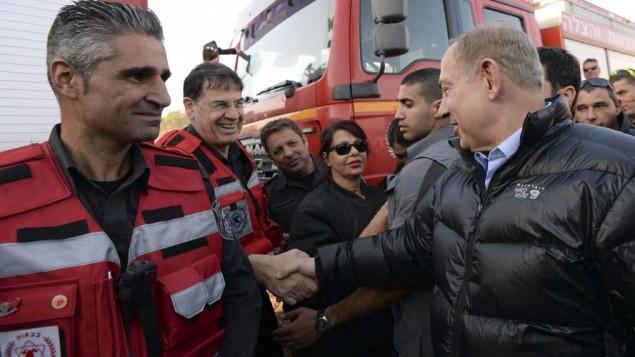 Le Premier ministre Benjamin Netanyahu avec les pompiers israéliens pendant sa visite au centre de commandement des incendies de Zichron Yaakov, le 23 novembre 2016. (Crédit : Haim Zach/GPO)