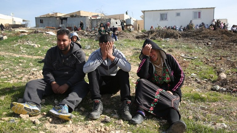Bedouins cry following the destruction of houses on January 18, 2017 in the Bedouin village of Umm al-Hiran. (AFP PHOTO / MENAHEM KAHANA) The Times of Israel