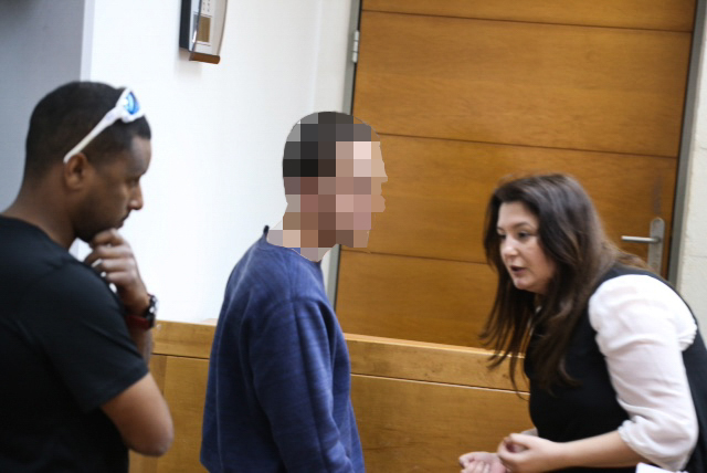 A Jewish Israeli teen is brought for a court hearing at the Rishon Lezion Magistrate's Court, on suspicion of issuing fake bomb threats against Jewish institutions in the US and around the world, on March 23, 2017. At right is his lawyer, Galit Besh (Flash90)
