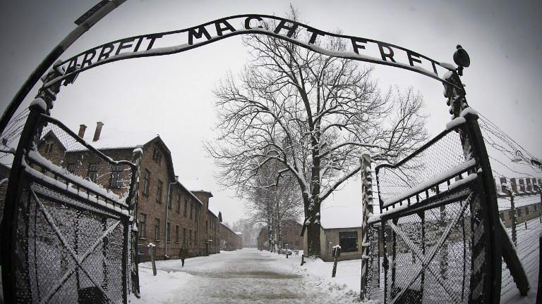 """L'entrée du camp d'extermination nazi d'Auschwitz-Birkenau avec le célèbre slogan """"Arbeit macht frei"""" (Le travail libère). (Crédit : Joël Saget/AFP)"""