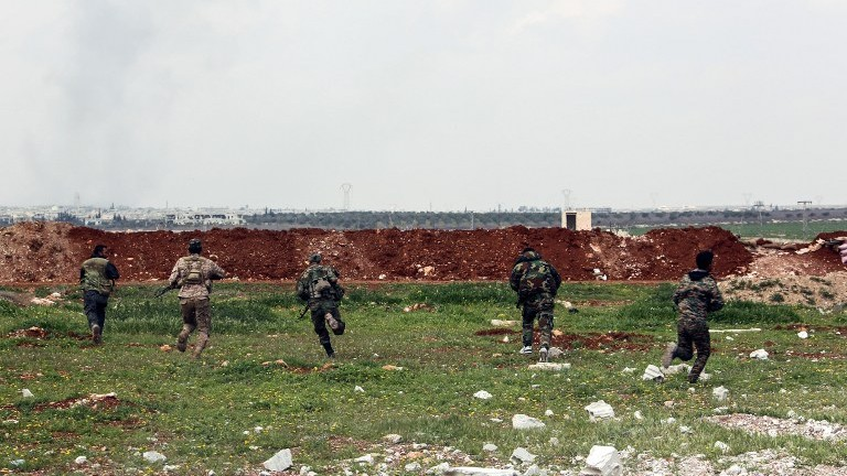 A picture taken on April 1, 2017 near the town of Qumhanah in the countryside of the central province of Hama, shows members of the Syrian government forces advancing towards the frontlines. (AFP Photo/Stringer)
