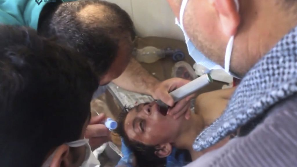 This frame grab from video provided on Tuesday April 4, 2017 shows a Syrian doctor treating a boy following a suspected chemical attack, in the town of Khan Sheikhoun, northern Idlib province, Syria. (Qasioun News Agency, via AP)