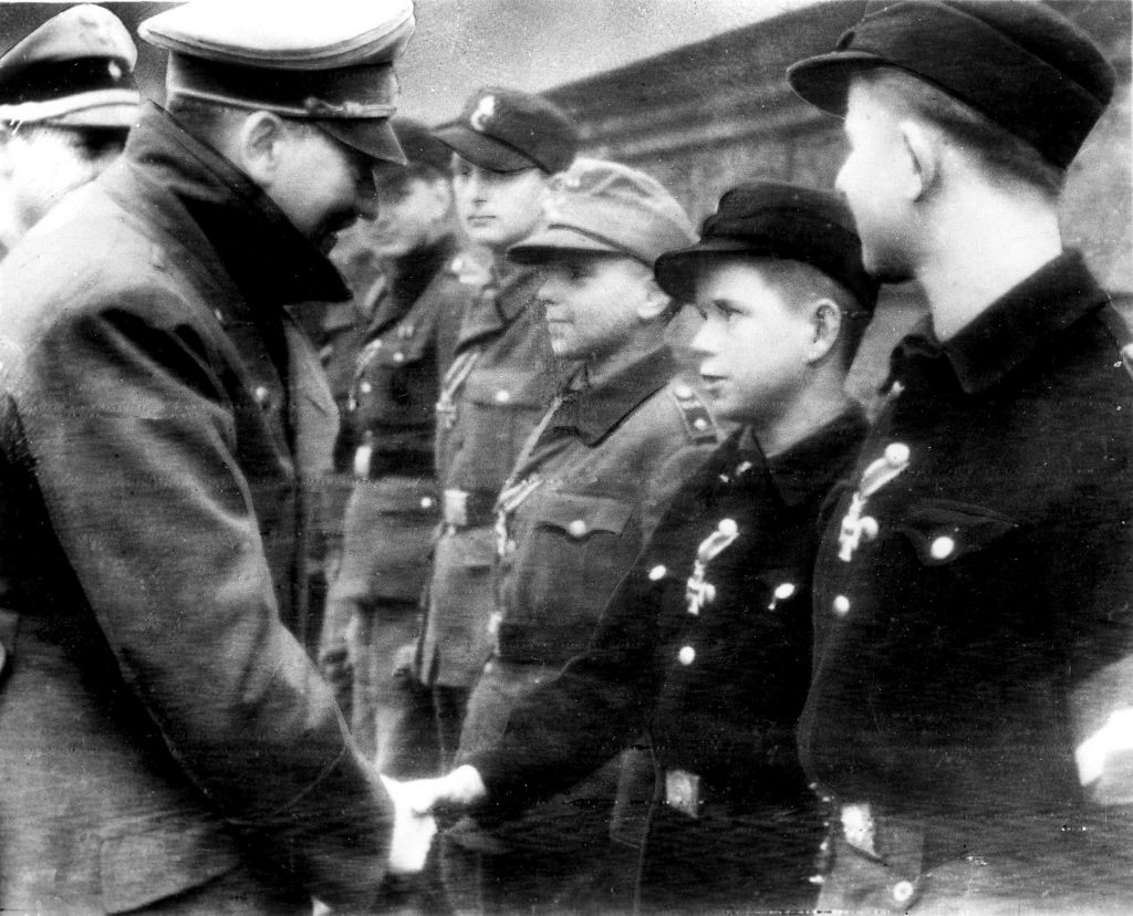 Adolf Hitler, left, shakes hands with 12-year-old Alfred Czech, a Hitler Youth soldier, after the young veteran of battles in Pomerania and Upper and Lower Silesia was awarded the Iron Cross at Hitler's headquarters in Germany on March 19, 1945, according to the German caption that accompanied the photo, taken by a Nazi photographer. The image is the last photo AP has of Hitler before his suicide a few weeks later. The photo was distributed by Buro Laux, a German Foreign Ministry conduit for photos, and transmitted to The Associated Press via the photo agency Pressens Bild in neutral Sweden. (Buro Laux/Pressens Bild via AP)
