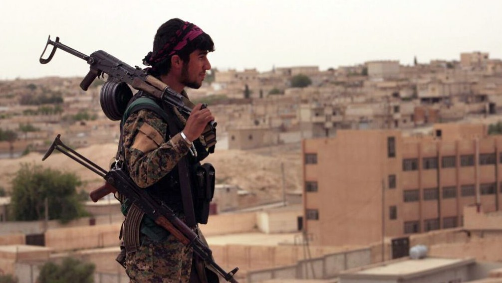 This April 30, 2017 photo shows a fighter from the SDF carrying weapons as he looks toward the northern town of Tabqa, Syria. (Syrian Democratic Forces, via AP)