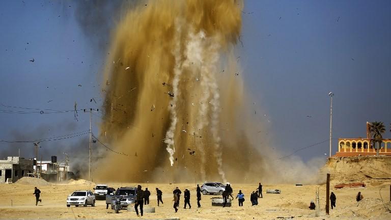 Les Palestiniens courent pour se protéger du nuage de sable et de la fumée suite à une attaque aérienne israélienne sur un poste du Hamas dans le nord de la bande de Gaza le 6 février 2017 (Crédit : Mohammed Abed / AFP)