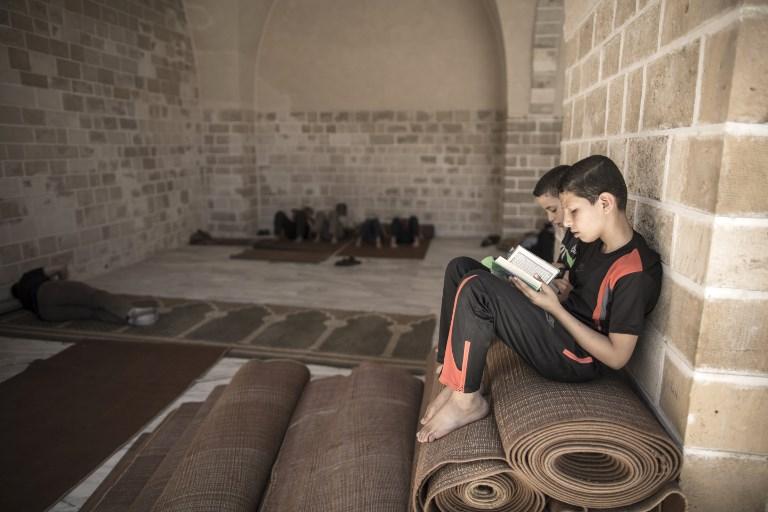Des enfants palestiniens lisent le Coran au premier jour de jeûne du Ramadan, à la mosquée al-Omari de Gaza Ville, le 27 mai 2017. (Crédit : Mahmud Hams/AFP)