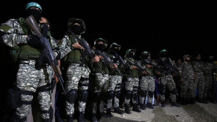 Fighters from the Ezzedine al-Qassam Brigades, the armed wing of the Palestinian Hamas terror movement, attend a memorial service for a commander killed in an apparently accidental explosion inn the southern Gaza Strip on June 10, 2017. (AFP/SAID KHATIB)