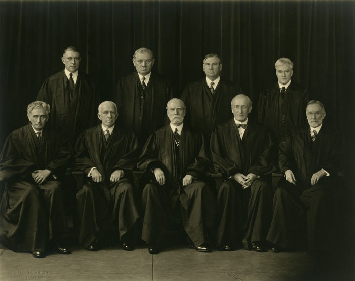 Posed group photograph, justices wearing robes of office. Seated, front row, far left, Louis Dembitz Brandeis; standing, back row, far right is Benjamin Nathan Cardozo. (Harris & Ewing/ Historical & Special Collections, Harvard Law School Library)