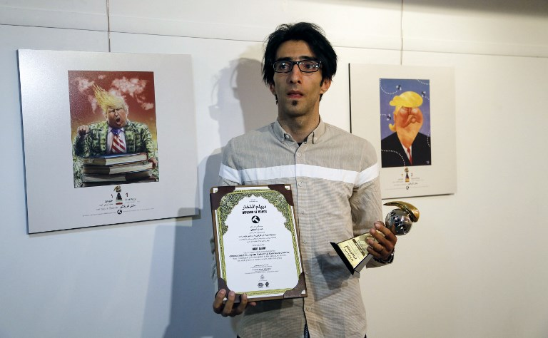 Iranian cartoonist Hadi Asadi poses for a picture with a trophy and an award next to cartoons of US President Donald J. Trump, at an exhibition of the Islamic Republic's 2017 International Trumpism cartoon and caricature contest, in the capital Tehran on July 3, 2017. (AFP PHOTO / ATTA KENARE)