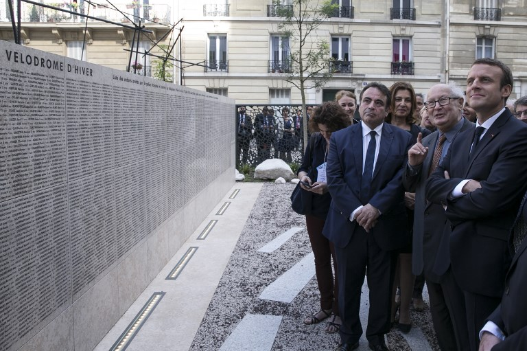 French President Emmanuel Macron (R) listens to Nazi hunter Serge Klarsfeld (2nd R) during a ceremony commemorating the 75th anniversary of the Vel d'Hiv roundup in Paris on July 16, 2017. (AFP PHOTO / POOL / Kamil Zihnioglu)