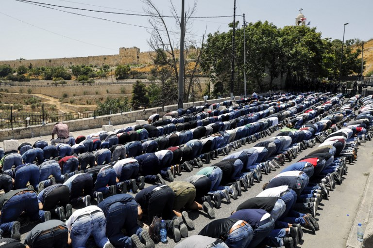 Muslim worshipers pray outside Jerusalem's Old City near the Lions' Gate on July 28, 2017. (AFP PHOTO / MENAHEM KAHANA)