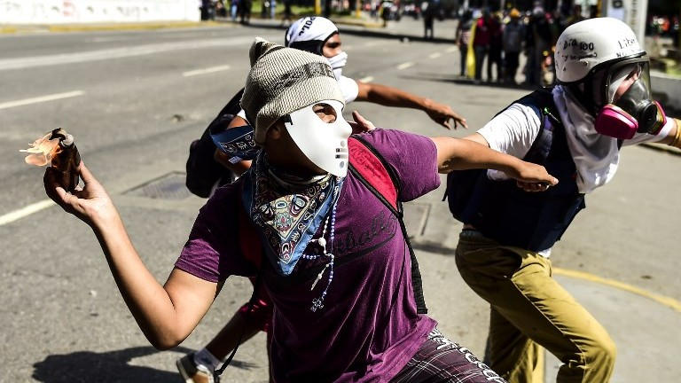 An opposition activist throws a Molotov cocktail during clashes with security forces in the Venezuelan capital of Caracas on August 12, 2017. (AFP Photo/Ronaldo Schemidt)