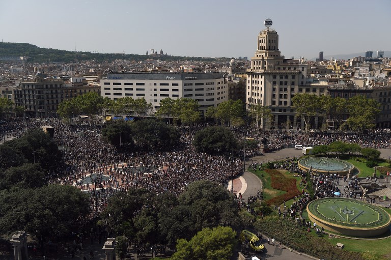 People leave the Plaza de Catalunya after observing a minute of silence for the victims of the Barcelona attack on August 18, 2017, a day after a van ploughed into the crowd, killing 13 persons and injuring over 100 on the Rambla in Barcelona.o / AFP PHOTO / LLUIS GENE