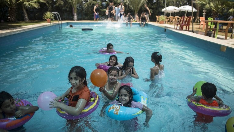 Palestinians spend time at the pool in Gaza City on July 24, 2017. (AFP Photo/Mahmud Hams)