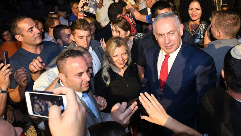 Prime Minister Benjamin Netanyahu (R) and his wife Sara (second from R) pose for photos with the crowd at an event event to mark 50 years of settlement in the West Bank at the Barkan Industrial Zone in the West Bank on August 28, 2017. (Kobi Gideon/GPO)