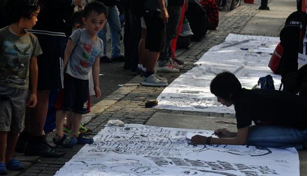 Seorang bocah melihat anggota Persatuan Kartunis Indonesia (Pakarti) yang sedang menggambar dengan tema Kota Jakarta di jalan MH Thamrin, Jakarta, Minggu (23/6). TEMPO/Eko Siswono Toyudho