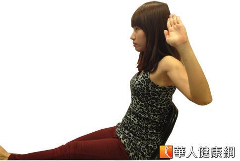 第3招:坐在椅子上,吸氣雙手向上伸展,舉起左腿與地面平行,腳跟用力向前踩。(攝影/黃子倫)
