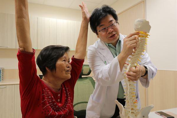李建裕醫師提醒趙阿嬤術後要經常手舉高做復健運動。(圖片提供/亞大醫院)
