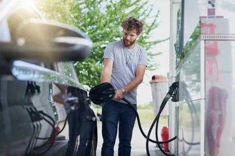 Hombre en la gasolinera llenando el depósito de su auto de combustible