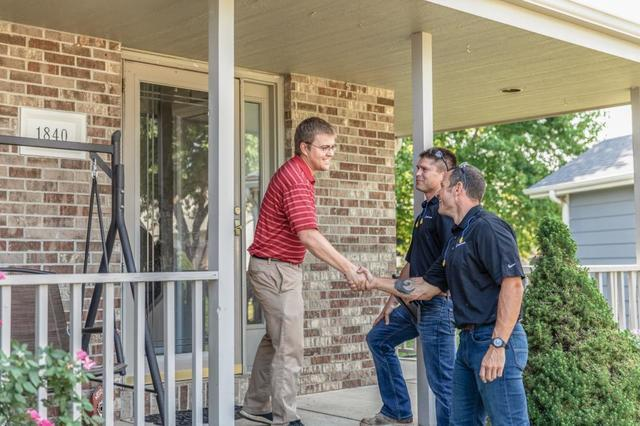Contractors meeting with a homeowner outside his home.