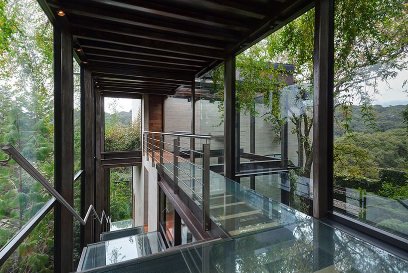 Outdoor Elevated Glass Walkway Connects Two Sections Of House