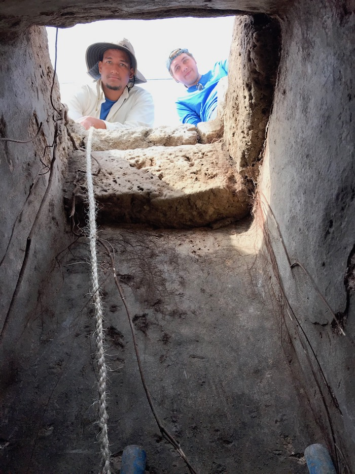 Vanderbilt students Niall Alvarado and Colin Bain peer down into a freshwater cistern, which indicated the homeowner's wealth