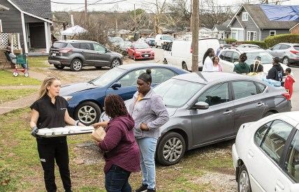 photo of students distributing supplies in neighborhood damaged by tornadoes