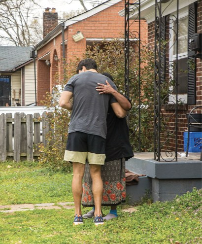 photo of a student hugging a woman whose neighborhood has been damaged by tornadoes