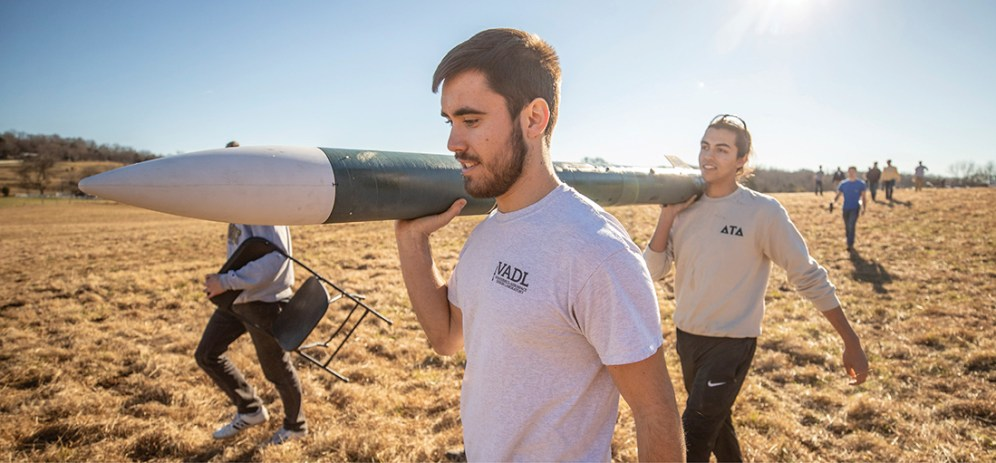 Chris Romanoski (foreground) and Henry Bristol carry the assembled subscale rocket to a practice launch rail to be readied for liftoff. This year's team practiced launches in December on some pasture land near Nashville. (Vanderbilt University/John Russell)