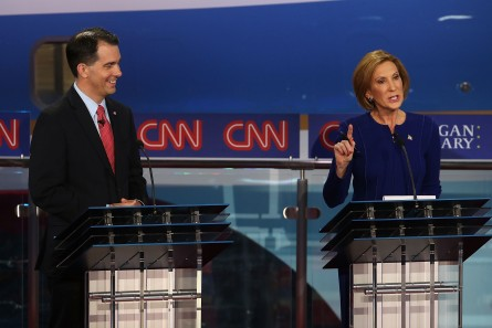 SIMI VALLEY, CA - SEPTEMBER 16:  Republican presidential candidate Wisconsin Gov. Scott Walker (L) looks on as Carly Fiorina speaks during the presidential debates at the Reagan Library on September 16, 2015 in Simi Valley, California. Fifteen Republican presidential candidates are participating in the second set of Republican presidential debates.  (Photo by Justin Sullivan/Getty Images)