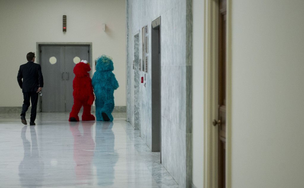 Sesame Street's Elmo, center, and Rosita, right, leave the Rayburn House Office Building after participating in a USO event to assemble care packages for troops overseas. (Bill Clark/CQ Roll Call)